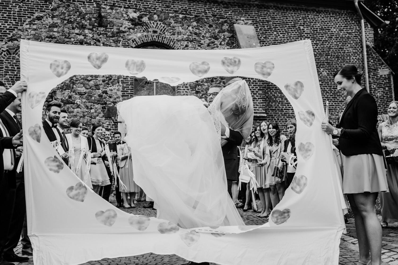 Brautpaar beim Durchsteigen eines Herzens im Laken