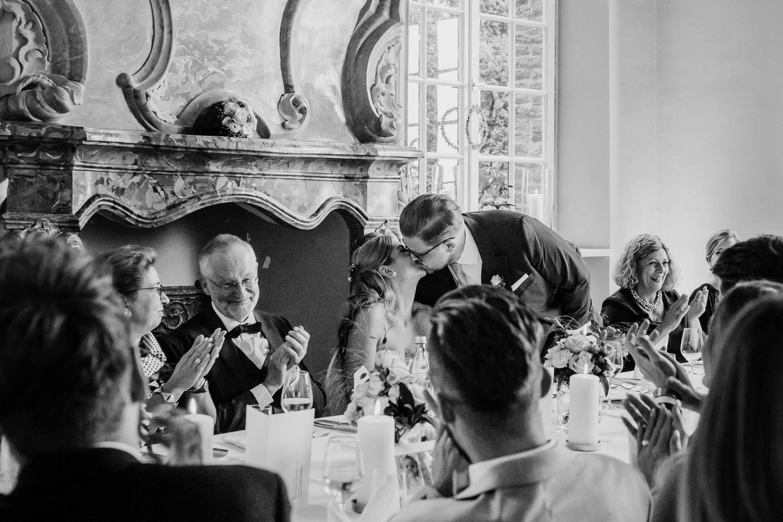 Hochzeitspaar , dass sich nach Tischrede küsst