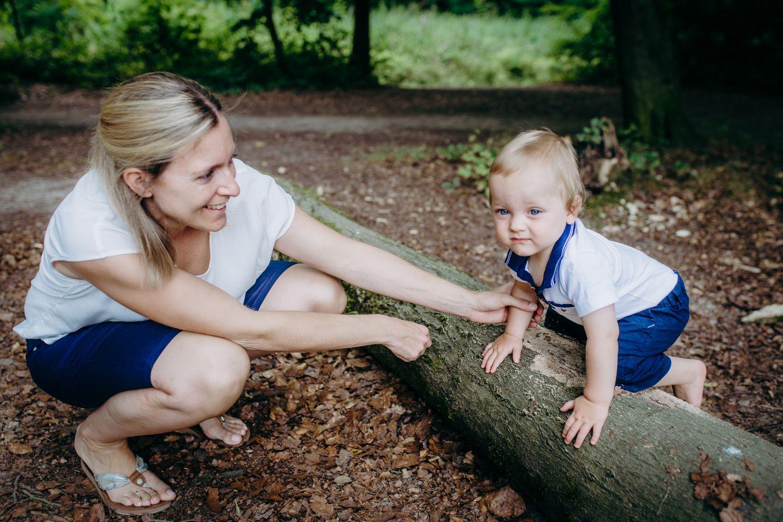kleiner Junge klettert über Baumstamm